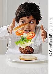 Little boy with hamburger ingredients in hands