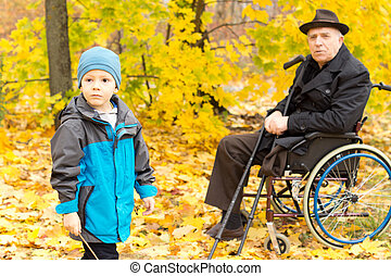 Little boy with his handicapped grandfather sitting in a wheelchair holding his crutches enjoying a day in nature together playing in colourful yellow autumn trees in a park