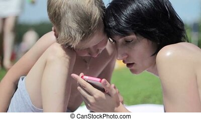 Little boy with his mother at a beach playing with a smartphone