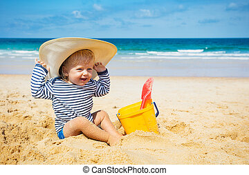 Little boy with huge straw hat sit on a sand beach