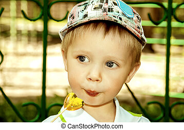 Little boy with lollipop in hand outdoors.
