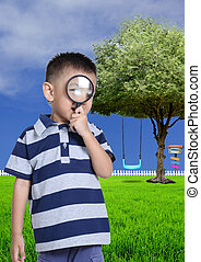 Little boy with magnifying glass in the garden.