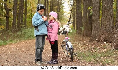Little boy with mobile phone and girl stand in park.