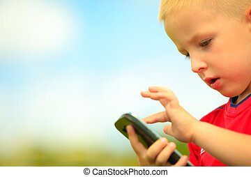 Little boy child kid playing games on smartphone mobile phone outdoor. Technology generation.