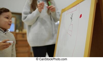 Little boy with mom in her living room house paint on the Board with markers a child's drawing. Leisure happy family. Pre-school education. close-up