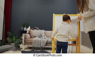 Little boy with mom in her living room house paint on the Board with markers a child's drawing. Leisure happy family. Pre-school education.