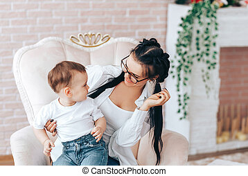 Little boy with mom sit in a chair