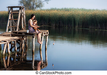 little boy with mother fishing on the lake - little boy with...