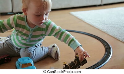 Little boy with mother playing with toy train