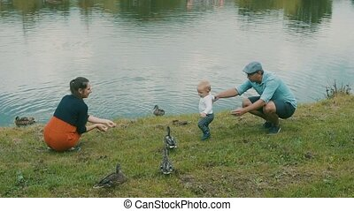 Little boy with parents making first steps. - Cute little...