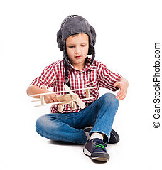 little boy with pilot hat and toy airplane