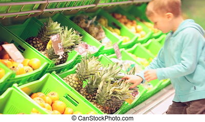 Little boy with pineapple - Boy quickly taking a pineapple...