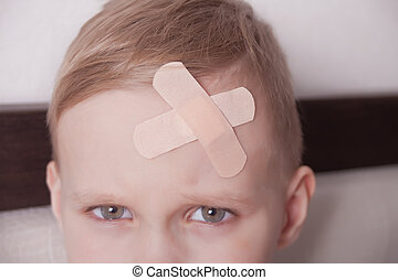 Little boy with plaster on head. Close up.