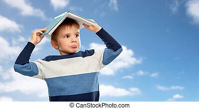 little boy with roof of book on his head over sky