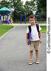 Little boy with school backpack and book posing in the play yard