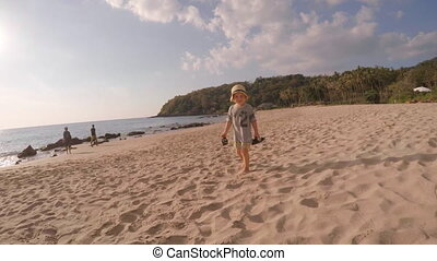 Little Boy with Shoes in Hands on the Beach