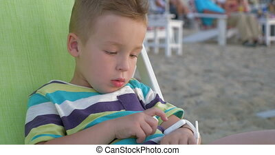 Little boy with smart watch sitting in deck chair