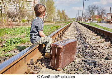 Little boy with suit case on railway