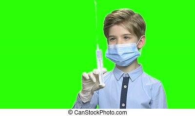 Little boy with syringe and protective mask. Portrait of a...