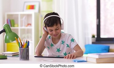 little boy with tablet pc and headphones at home -...