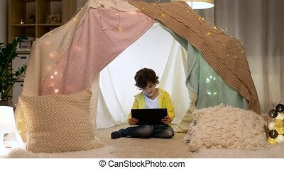 little boy with tablet pc in kids tent at home - childhood,...