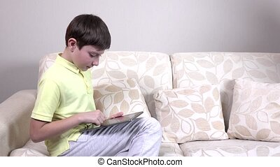 Little boy with tablet sitting on a sofa at home
