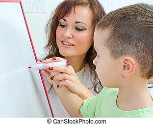 Little boy with teacher near whiteboard