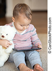 Little boy with teddy bear and tablet.