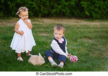 little boy with the girl and rabbit playing in the grass