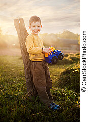 little boy with toy car at nature, warm evening light, childhood illustrations
