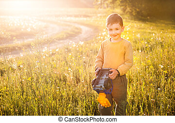 little boy with toy car on field spring warm, evening light, childhood illustrations