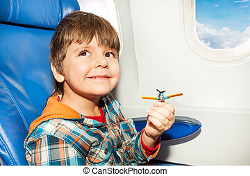 Little boy with toy plane fly in airplane