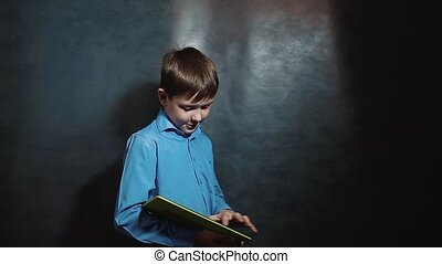 little boy works on tablet web internet business. Young...