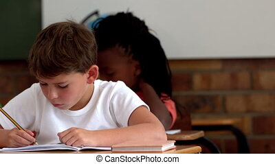 Little boy writing in notepad