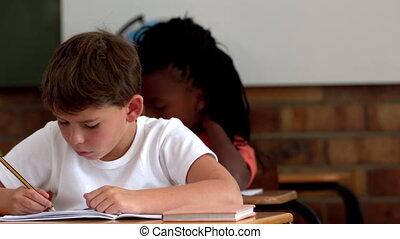 Little boy writing in notepad in classroom in slow motion