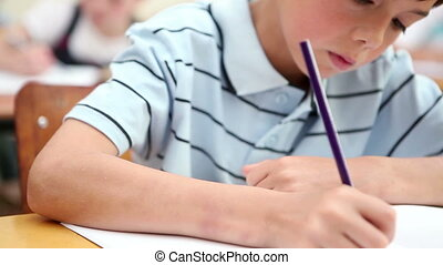 Little boy writing on his notebook
