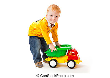 little boyplays with toy truck