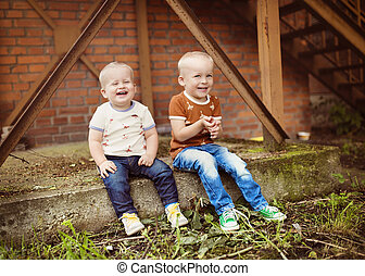 Little boys - Cute little boys sitting outside on a concrete...