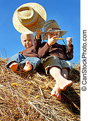 Little Boys in Straw Hats Sitting on Hay Bales