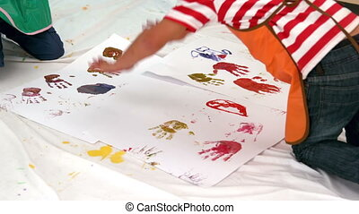 Little boys painting lying on paper - Cute little boys...