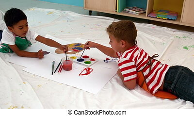 Little boys painting lying on paper