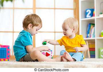 little boys play together with educational toys