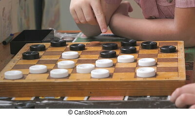Little boys sit at the table and play checkers at the garden. Close-up