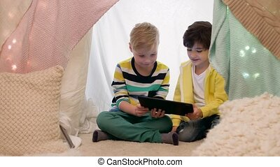 little boys with tablet pc in kids tent at home