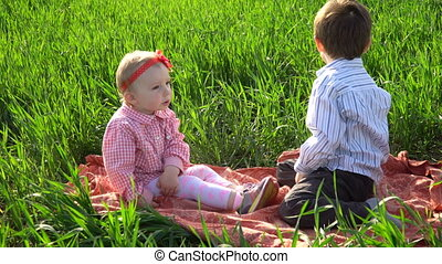 Little brother and sister are sitting on a blanket in the field
