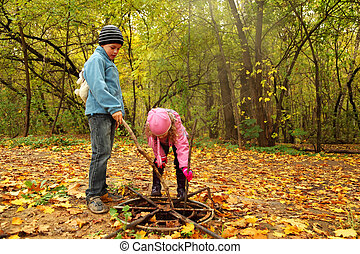 little brother and sister in autumn park poke sticks in old...