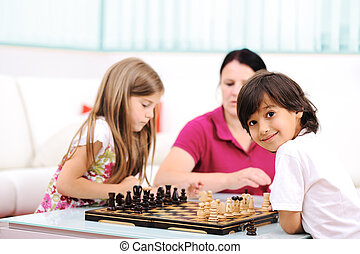 Little brother and sister playing chess at home with their mother