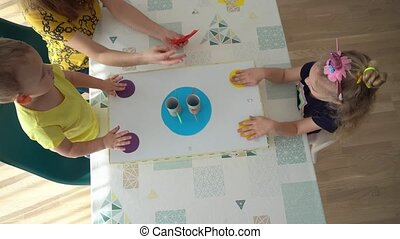 Little brother and sister playing diy crafts sumo wrestler board game on table. In a modern living room a beautiful mother with her two kids spending a great time together. Gimbal movement shot.