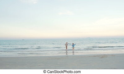 Little brother and sister running out of the sea