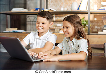 Little brother and sister surfing the web together